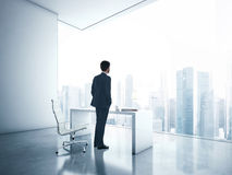 Businessman looking megalopolis through window Stock Photo