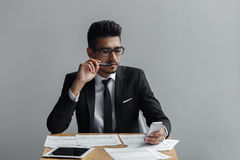 Businessman looking at mobile phone with a pen in his mouth. Royalty Free Stock Images