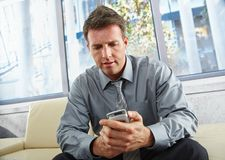 Businessman looking at mobile on sofa. Stock Photos
