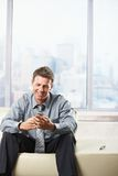 Businessman looking at mobile on sofa. Stock Photo