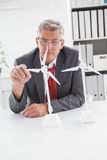 Businessman looking at model wind turbines. In his office Royalty Free Stock Photo