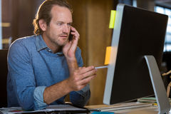 Businessman looking at monitor while talking on cellphone Royalty Free Stock Photography