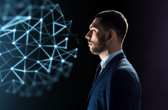 Businessman looking at network virtual projection. Business, network, people and technology concept - businessman in suit looking at virtual low poly projection Royalty Free Stock Image