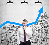 Businessman is looking for new business ideas. Blue growing arrow as a concept of successful business. Business icons are drawn on the concrete wall Stock Images