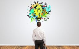 Businessman looking for new idea. Businessman looking to a wall with new idea concept stock photos