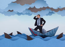 Businessman looking for new opportunities. And sailing in stormy papers sea. Paper waves, clouds, boat and sharks Stock Photo