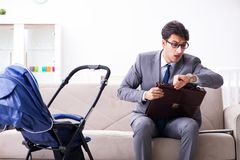 The businessman looking after newborn baby at home and teleworking Stock Photo