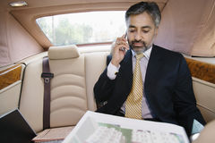 Businessman Looking At Notepad While On Call In Car Stock Photos