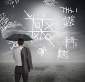 Businessman looking at noughts and crosses. And holding umbrella Royalty Free Stock Image