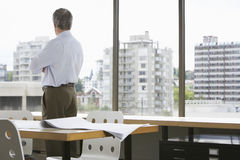 Businessman Looking Through Office Window Stock Photos