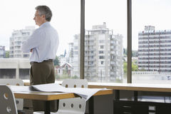 Businessman Looking Through Office Window Royalty Free Stock Photography
