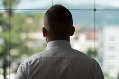 Businessman Looking Through Office Window Royalty Free Stock Image