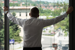 Businessman Looking Through Office Window Royalty Free Stock Images