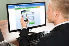 Businessman looking at online tax return form Royalty Free Stock Images