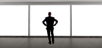 Businessman Looking Out a Big Window Royalty Free Stock Image