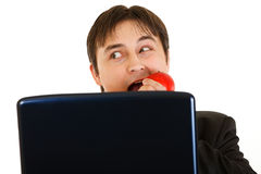 Businessman looking out from laptop and eating Royalty Free Stock Photography