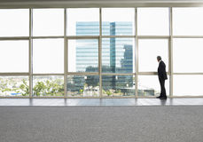 Businessman Looking Out Of Office Window Stock Photo