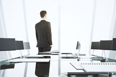 Businessman looking out the window in modern conference room wit Royalty Free Stock Image