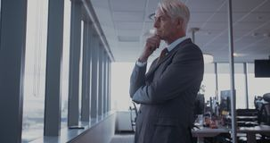 Businessman looking outside the window and thinking stock video