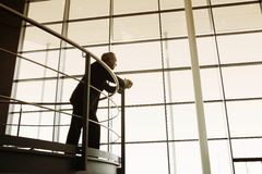 A businessman looking over balcony railings in a modern office building Stock Photos