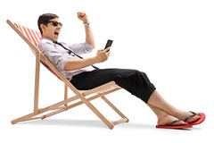 Businessman looking at a phone and gesturing happiness. Businessman sitting in a deck chair looking at a phone and gesturing happiness isolated on white Royalty Free Stock Photo