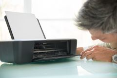 Businessman looking in photocopy machine Royalty Free Stock Photos