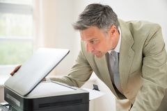 Businessman looking at photocopy machine Royalty Free Stock Photo