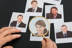 Businessman looking at  photograph through magnifying glass Royalty Free Stock Image