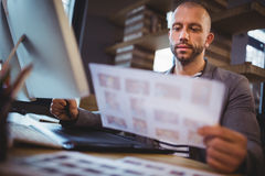 Businessman looking at photographs while using graphics tablet Royalty Free Stock Image