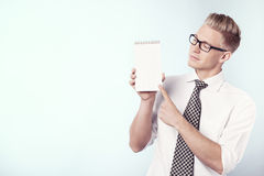 Businessman looking and pointing finger at empty notepad. Handsome young businessman pointing finger at blank notebook with space for text while looking at it Royalty Free Stock Photos