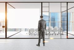 Businessman looking at a poster in office. Rear view of a businessman looking at a blank poster hanging on a white office wall near a panoramic window. 3d Stock Photography