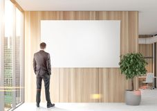 Businessman looking at a poster in wooden office. Rear view of a businessman looking at a blank poster hanging on a wooden office wall near a panoramic window Royalty Free Stock Image
