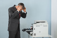 Businessman Looking At Printer Machine At Office Stock Photography
