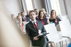 Businessman looking at public speaker during seminar in convention center stock photos