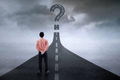 Businessman looking at question mark on the road Royalty Free Stock Images