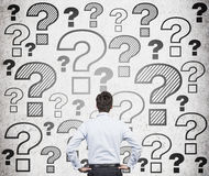 Businessman looking at question marks. Businessman looking at drawing question marks on wall Royalty Free Stock Photo