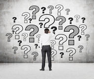 Businessman looking at question marks. Businessman looking at drawing question marks on wall Stock Photos