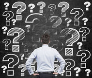 Businessman looking at question marks. Young businessman looking at drawing question marks on wall Stock Photo