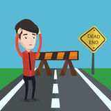 Businessman looking at road sign dead end. Young businessman having trouble in business. Desperate businessman clutching his head while standing in front of Stock Photography