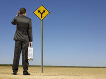 Businessman Looking At Road Sign On Desert Stock Image