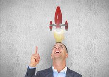 Businessman looking at rocket over head Stock Photo