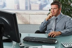 Businessman looking at screen in office Stock Photo