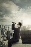 Businessman looking at sky with binocular Stock Photo