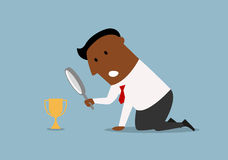 Businessman looking at small trophy with magnifier Royalty Free Stock Photography