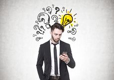 Businessman looking at smartphone, questions, idea Royalty Free Stock Image