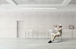Businessman looking in spyglass Stock Photo