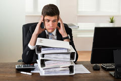 Businessman Looking At Stack Of Folders Royalty Free Stock Photos