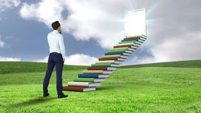 Businessman looking at stair made of books on a green field stock video footage