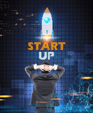 Businessman looking at a start up rocket Stock Image
