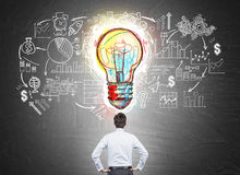 Businessman looking at start up sketch on chalkboard. Rear view of businessman in shirt looking at startup sketch on blackboard with large colorful light bulb Stock Photography